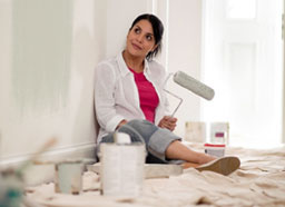 Woman taking a break from paiting a wall, smiling.